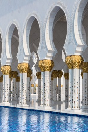 Hallway with golden decorated pillars at the entrance of the world famous landmark Sultan Sheikh Zayed Mosque in Abu Dhabi, UAE