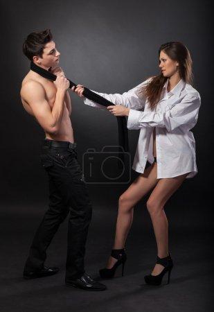 Photo pour Belle fille dans une chemise blanche tire un homme pour une cravate sur fond foncé - image libre de droit