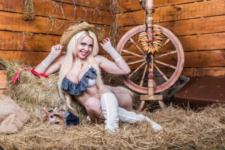 Photo for Young sexy girl in underwear and white boots sit with dog in the barn on hay - Royalty Free Image