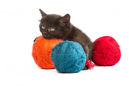 Black kitten playing with a red ball of yarn