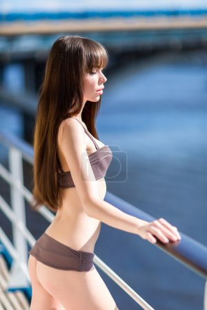 Sexy woman in stylish swimsuit standing on the aft of a sailing