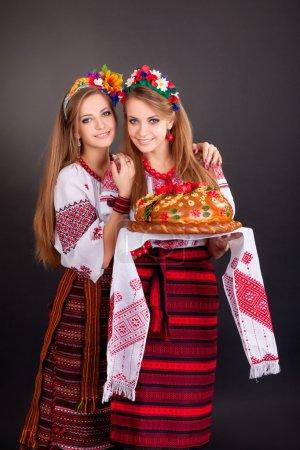 Photo pour Jeunes femmes en vêtements ukrainiens, avec guirlande et pain rond sur fond noir - image libre de droit