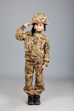 Saluting soldier. Young boy dressed like a soldier