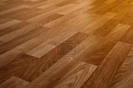 The floor of the light brown laminate diagonally...