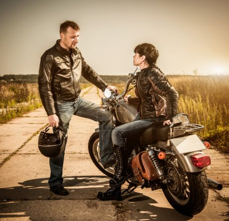 Photo for Biker man and girl sits on a bike - Royalty Free Image