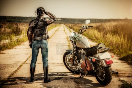 Photo for Biker girl stands on the road and looks into the distance - Royalty Free Image