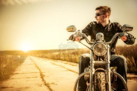 Photo for Biker man sits on a bike - Royalty Free Image