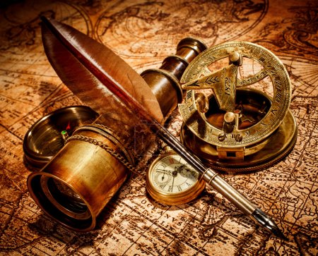 Photo for Vintage compass, goose quill pen, spyglass and a pocket watch lying on an old map. - Royalty Free Image