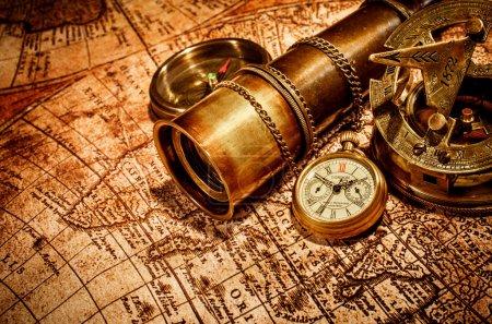 Photo pour Vintage boussole,, verre espion et une montre de poche couché sur une vieille carte . - image libre de droit