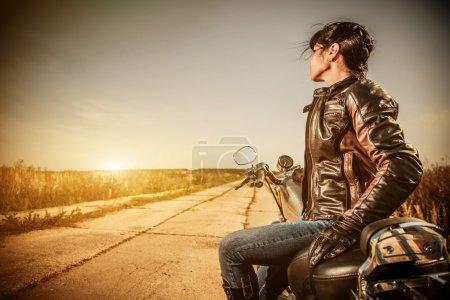 Photo pour Fille de motard dans une veste en cuir sur une moto en regardant le coucher du soleil. - image libre de droit
