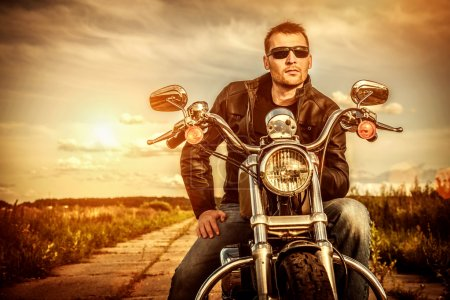 Photo for Biker man wearing a leather jacket and sunglasses sitting on his motorcycle looking at the sunset. - Royalty Free Image