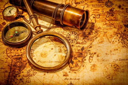 Photo for Vintage magnifying glass, compass, telescope and a pocket watch lying on an old map. - Royalty Free Image