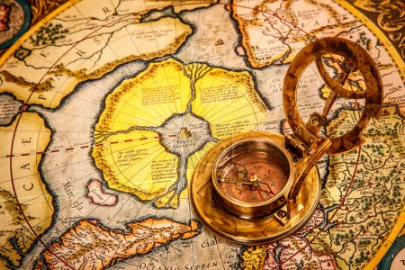 Vintage compass lies on the ancient map of the North Pole (also