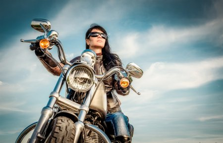 Photo for Biker girl in a leather jacket on a motorcycle looking at the sunset. - Royalty Free Image