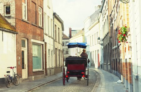 Tourists in a phaeton go on ancient streets of Bruges, Belgium. Painting imitation