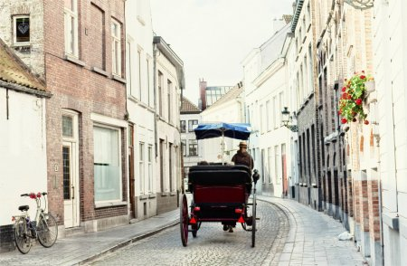 Tourists in a phaeton go on ancient streets of Bruges, Belgium. Painting imitation.