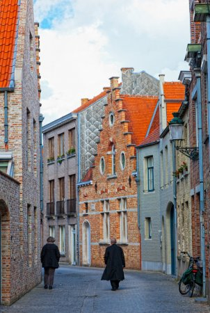 Two persons go on the old street to Bruges, the wall has a bicycle