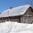 Traditional old log cabin covered with snow, snowd...