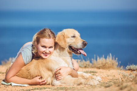 Young woman, labrador dog, sea