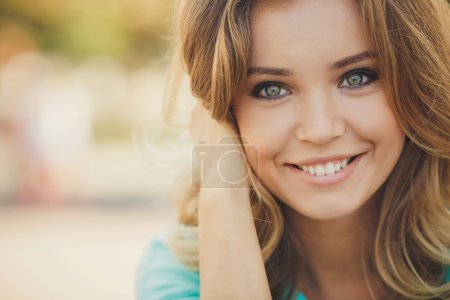 Portrait of a young beautiful smiling blonde woman outdoors