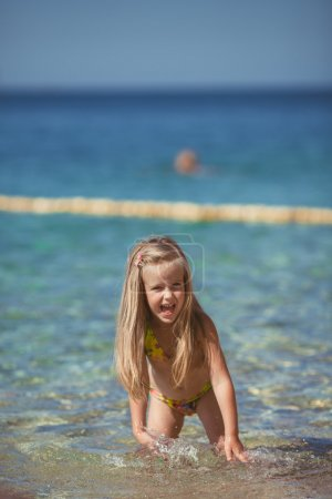 Photo for Six year old blonde girl in a bathing suit with her hair sitting on the beach near the water - Royalty Free Image