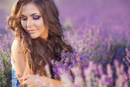 Photo for Beautiful provence woman relaxing in lavender field watching on sunset holding basket with lavanda flowers. Series. alluring girl with purple lavender. blond lady in blossom field . Ukraine - Crimea - Royalty Free Image