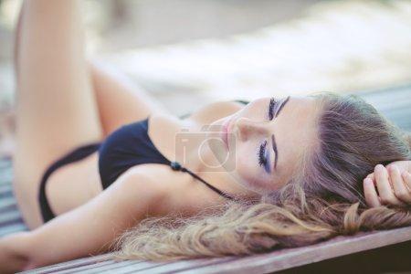 Portrait of woman sunbathing in bikini at tropical travel resort