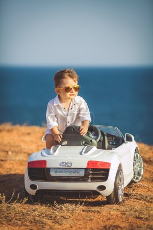 Photo for Portrait of a little boy in a child car in summer near the sea - Royalty Free Image