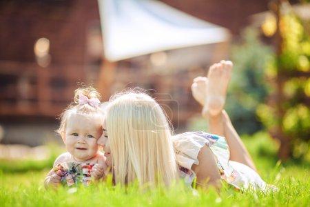 Photo pour Portrait de la mère avec sa fille infantile bébé jouer sur l'herbe en plein air parc verdoyant de l'été - image libre de droit