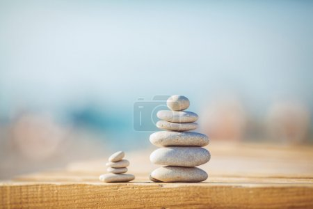 Photo for Zen stones jy wooden banch on the beach near sea. Outdoor - Royalty Free Image