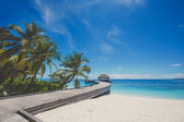 Landscape of tropical island beach with perfect sky, palms, traditional buildings
