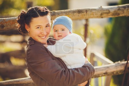 Portrait of Young mother and her cute girl having fun i on a countryside n autumn