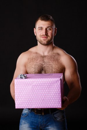 Photo for A young strong muscular man with a beautiful gift box and ribbon - Royalty Free Image