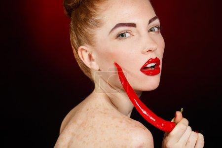 Photo pour Belle femme séduisante fille de mode avec des lèvres rouges tenant un piment rouge noir fond studio shot - image libre de droit