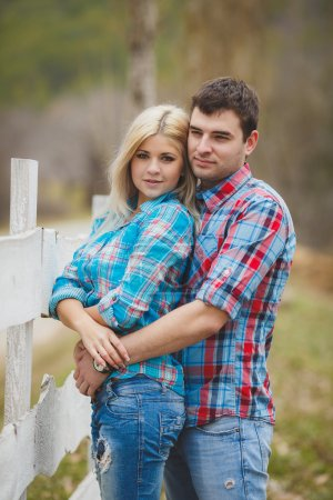 Portrait of happy young couple wearing shirts having fun outdoors near fence in park