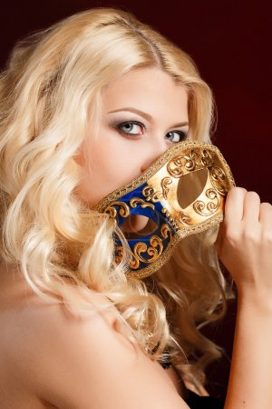 Portrait of a beautiful young blond woman with theatrical mask on his face on a dark background