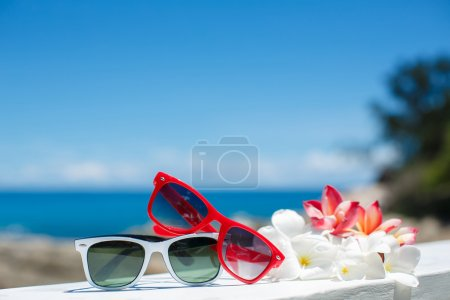 Photo for Two pair of sun glasses on a beach table on blue ocean background - Royalty Free Image