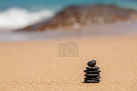 Zen stones jy on the sandy beach near the sea.