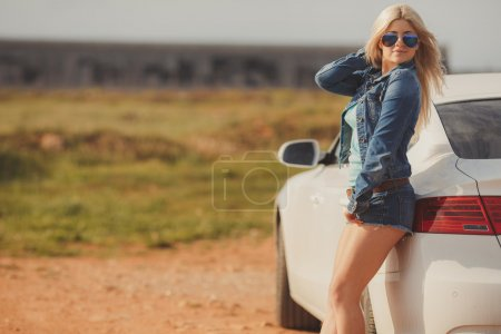 Portrait of a young pretty blonde with luxury car