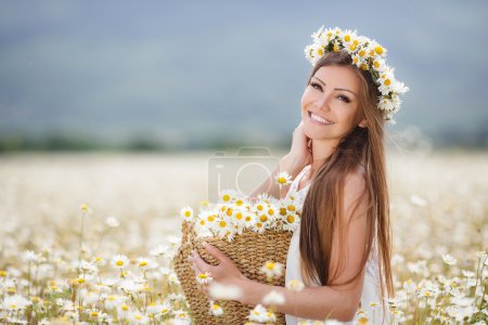 Beautiful girl on the camomile field