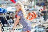 Krásná sexy blond žena nosí námořník pruhované šaty pózuje u člunů