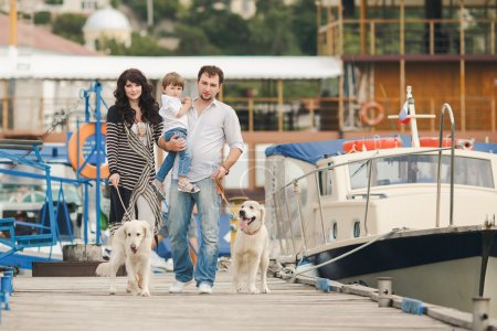 Happy family with dogs on the Quay in the summer