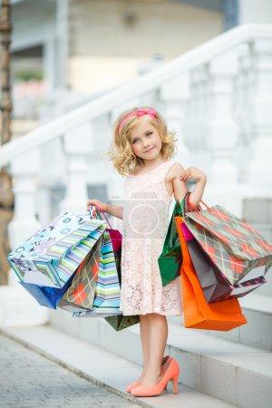 Photo pour Joyeux préscolaire fille marche avec des sacs à provisions. Jolie petite fille souriante avec des sacs à provisions avec pouce vers le haut signe dans la boutique - image libre de droit