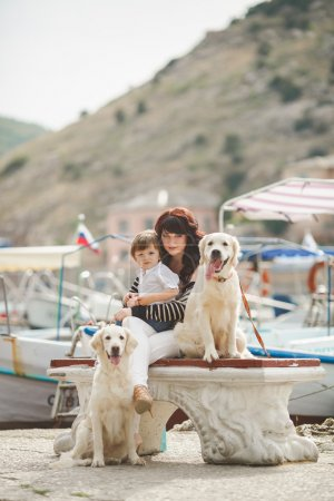 Mother and son on the waterfront with a dog