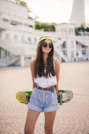 Photo for Sunny fashion outdoor urban portrait of pretty brunette fashion woman in city. Beautiful hipster girl with skate board wearing sunglasses. Beautiful and fashion young woman posing with a skateboard - Royalty Free Image