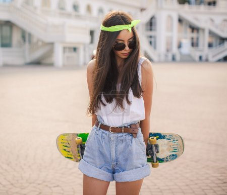 Beautiful and fashionable young woman posing with skateboard