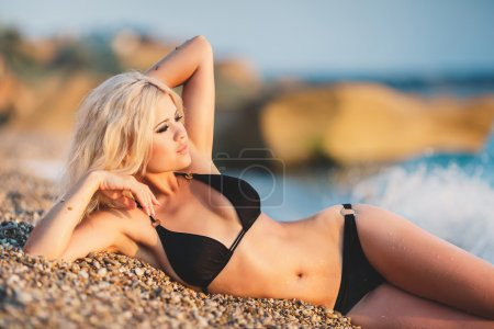 A beautiful young woman resting on the beach.