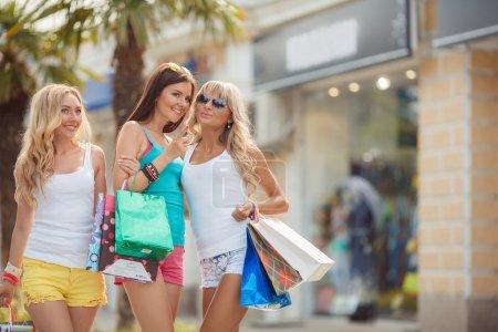 Photo pour Grandes ventes. Trois filles tenant des sacs à provisions et se promenant dans les magasins. Copines souriantes s'amuser ensemble et regarder en arrière face à la caméra - image libre de droit