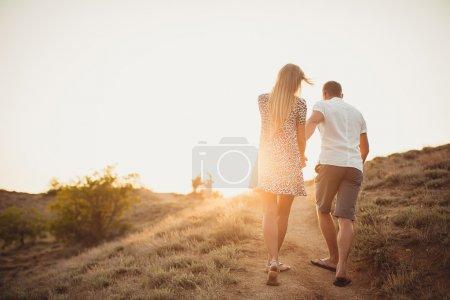 Photo pour Jeune couple amoureux, un homme et une femme séduisants profitant d'une soirée romantique, se tenant la main pour regarder le coucher de soleil - image libre de droit