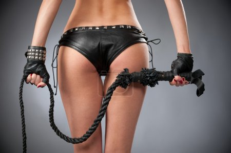Half body shot of sexy womans buttocks in black underwears on gray background with a whip in his hand